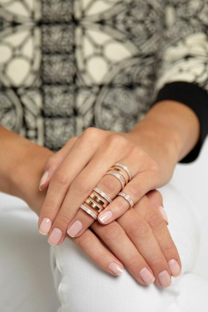 une grosse bague en or rose portée sur la phalange, anneaux élégants pour mettre en valeur le vernis nude