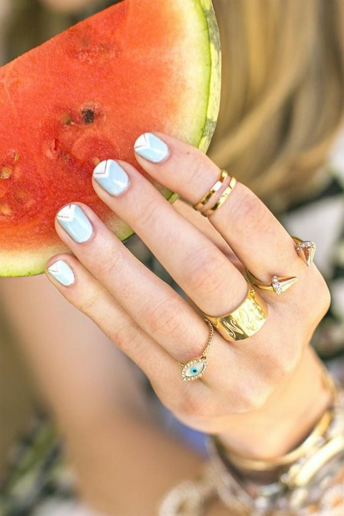 une fine bague double portée sur le bout du doigt, nail art graphique couleur pastel