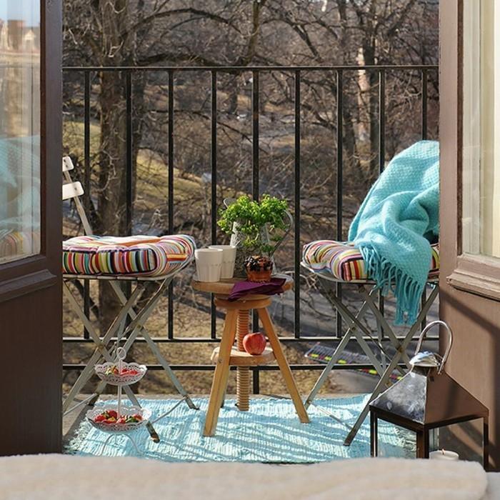 decoration balcon, tapis turquoise, couverture à franges, table ronde en bois, tasses de café