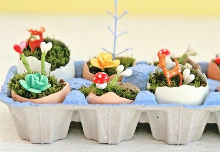 mini-jardin-dans-une-coquille-d-oeuf-coquilles-posées-dans-une-boite-a-oeufs-mousse-petits-fleurs-et-figurines-décoratifs-activité-manuelle-paques