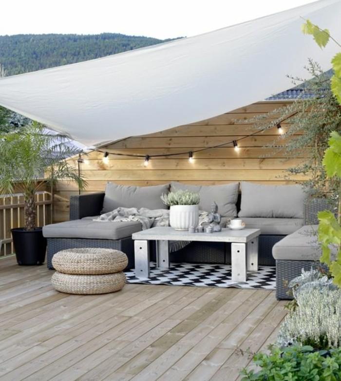 terrasse tropézienne en bois, canapé d angle, pouf, tapis en noir et blanc à motifs géométriques, plantes, guirlande lumineuse, lambris