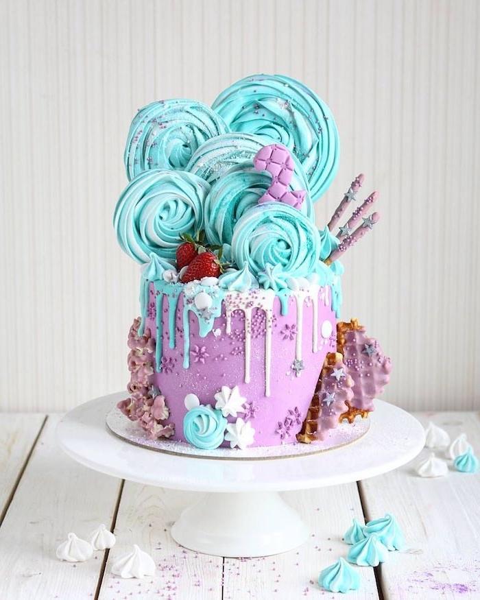 magnifique gateau anniversaire enfant aux tons pastel motif mer et sièren avec meringues bleus en top, glácage blanc et bleu et base violette