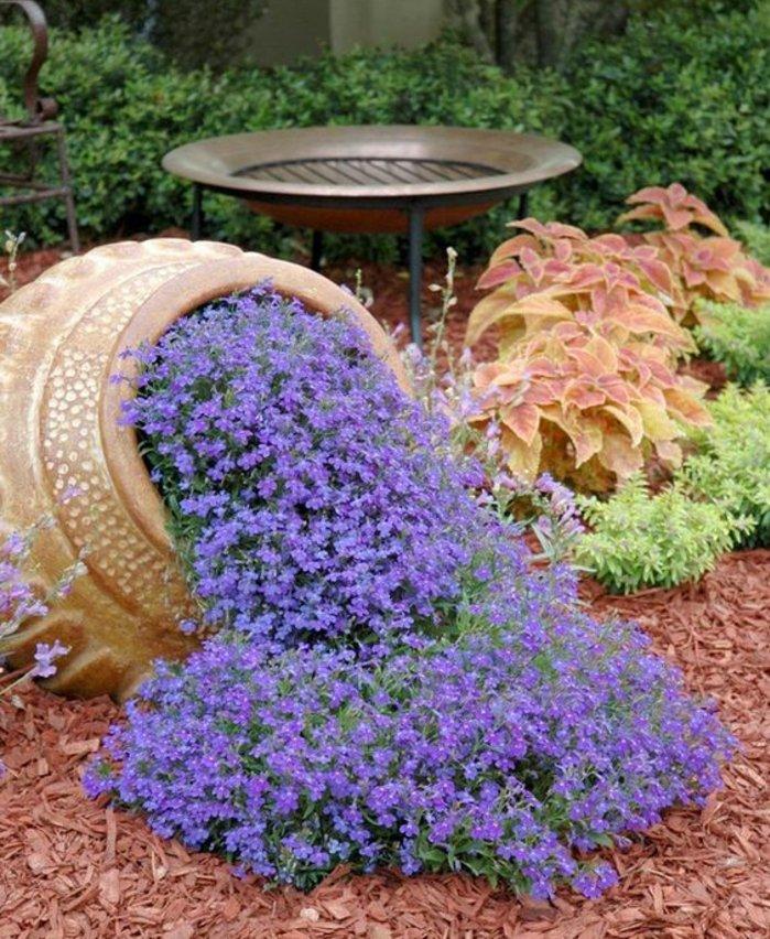 un vase en terre vintage énorme avec des fleurs plantés dedans et par terre, idée parterre fleuri intéressante