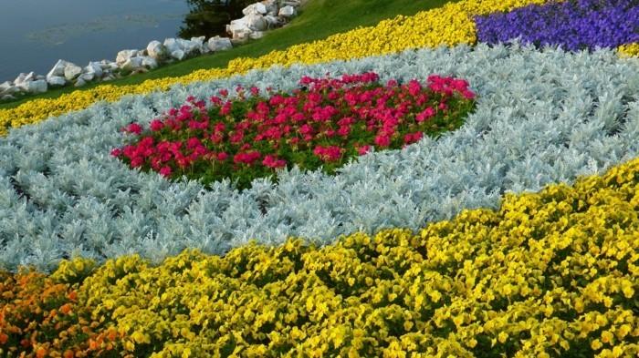 idée de génie jardin original, gazon en pente, fleurs roses, jaunes, oranges et arbustes bleus, pierres, comment faire un parterre de fleurs