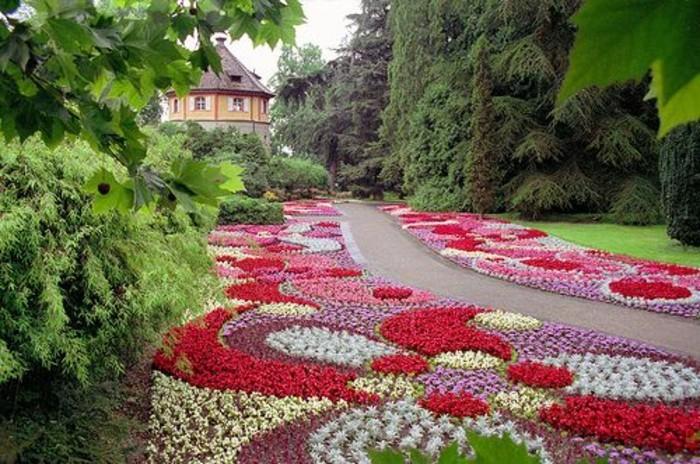parterre de fleur, fleurs rangées en forme de fleurs, arbres, arbustes, allée, maison vintage, idée de génie jardin