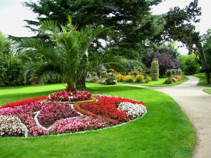fleurs rose, blanches et rouges avec un palmier au milieu,arbres, gazon, idée de parterre fleuri dans un jardin énrome