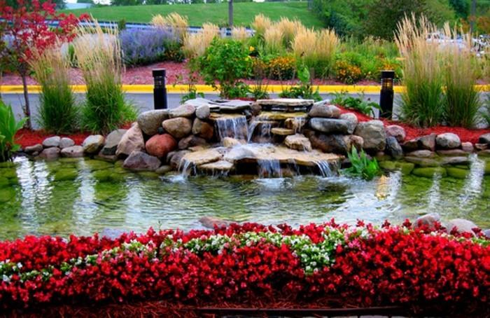 bordure parterre de fleurs rouges, vertes et blanches, pierres, chute d'eau, idée coin détente naturel en plein air