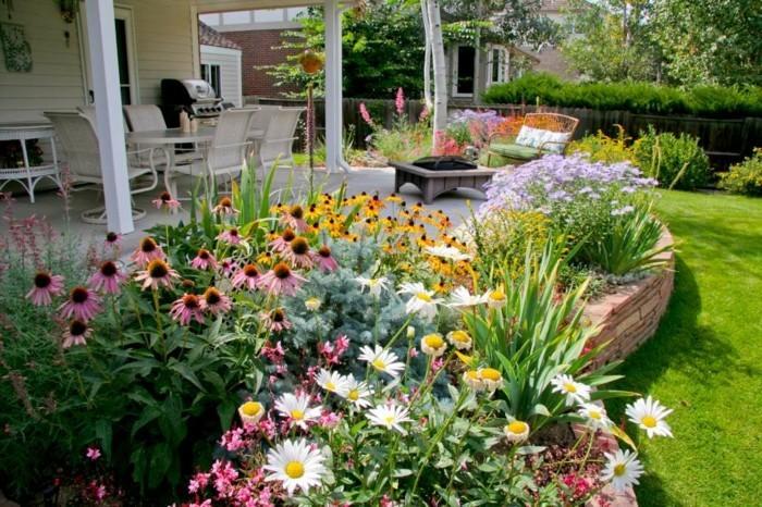 parterre fleuri avec des marguerites et autres fleurs, aux abords d'une terrasse, idee jardin aménagement floral