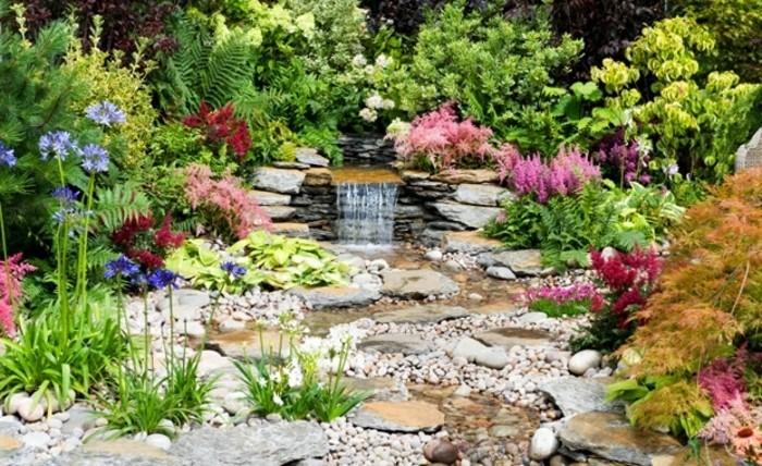 petit-bassin-d-eau-entouré-de-végétation-fleur-de-rocaille-différents-genres-de-fleurs-violettes-rouges-et-rose