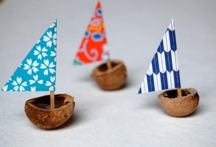 un petit bateau fabriqué à partir de coquille de noix, avec mât en papier et coton tige, idée activité manuelle maternelle, inspiration bord de mer