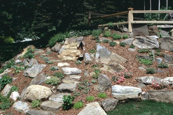 rocaille-fleurie-grosses-pierres-fleurs-et-plantes-vertes-sur-une-surface-en-pente-allée-en-pierre