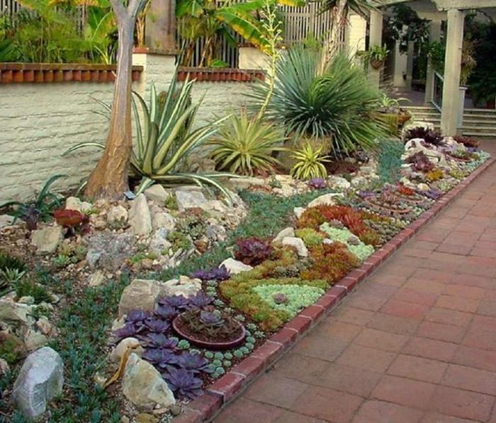 rocaille-fleurie-longeant-une-allée-idée-comment-faire-une-rocaille-de-succulents-de-couleurs-divers-arbustes-et-pierres