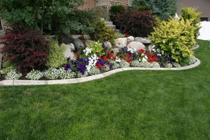 rocaille fleuri, parterre de fleur, en combinaison avec des arbustes, parterre aménagée près de l'entrée d'une maison, gazon