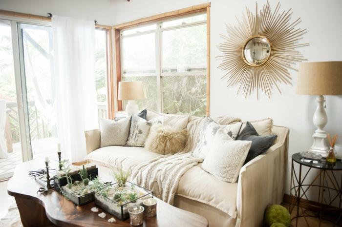 ambiance cocooning, murs blancs, miroir soleil, grande fenêtre, canapé beige, lampe beige