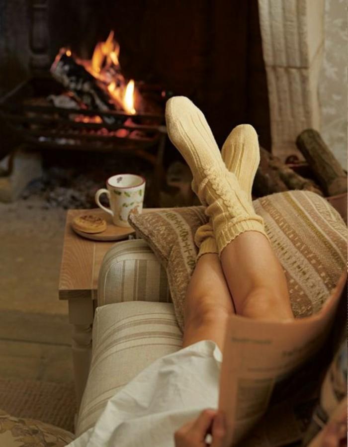 salon-cocooning-canapé-cheminée-journal-coussin-table-en-bois