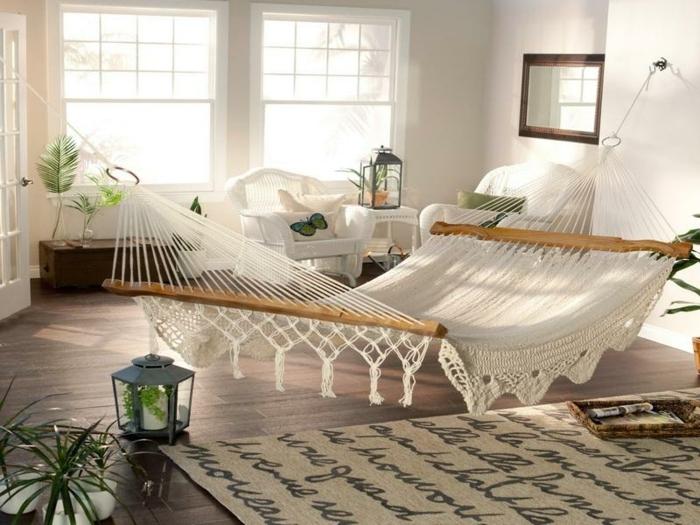 décoration intérieure salon, hamac grand, tapis beige, grande fenêtres, plantes vertes, lanterne à bougies