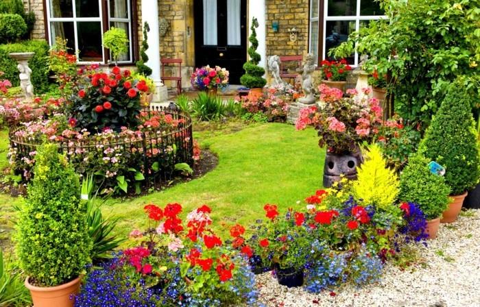 plusieurs fleurs dans des pots de fleurs et une parterre en forme ronde au milieu d'un gazon, petites sculptures, decoration exterieur abondante