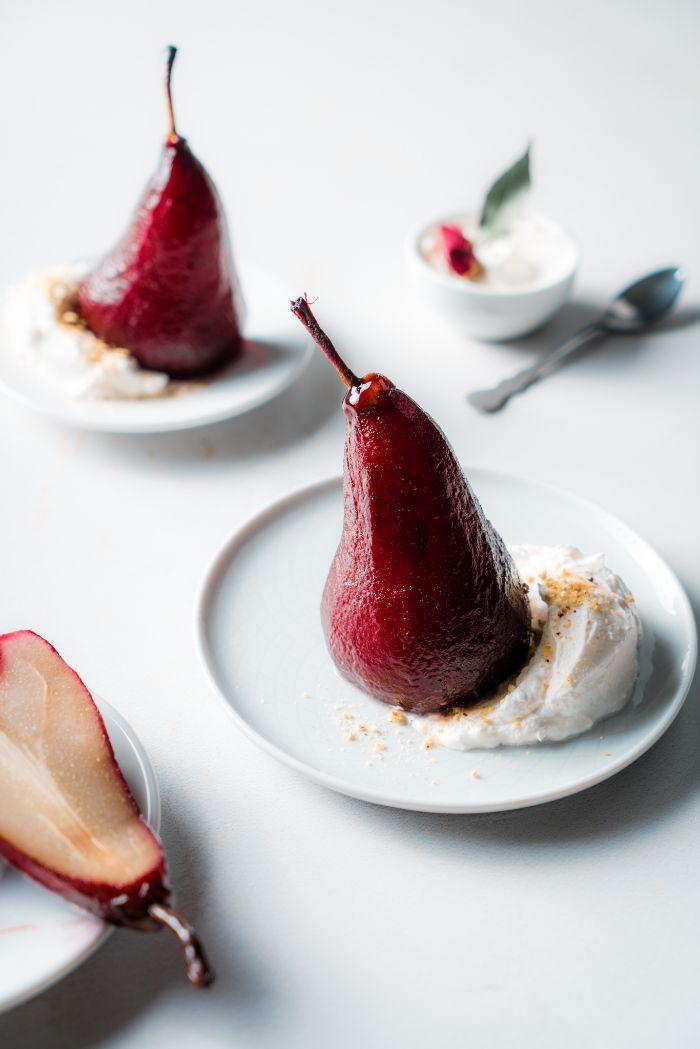 servir une poire pochée avec de la creme fraiche dans une assiette blanche, recette diner romantique à la maison