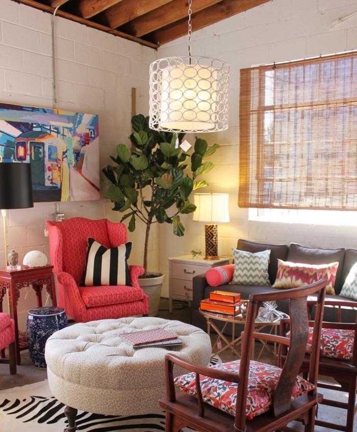idee deco salon cocooning, fauteuil rose, plafond avec poutres en bois, canapé gris foncé