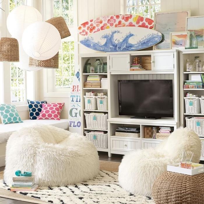 canapé cocooning, grands poufs en fausse fourrure, panier en paille, tapis blanc et noir, coussins décoratifs