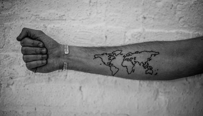 tatouage carte du monde sur le bras style tattoo voyage