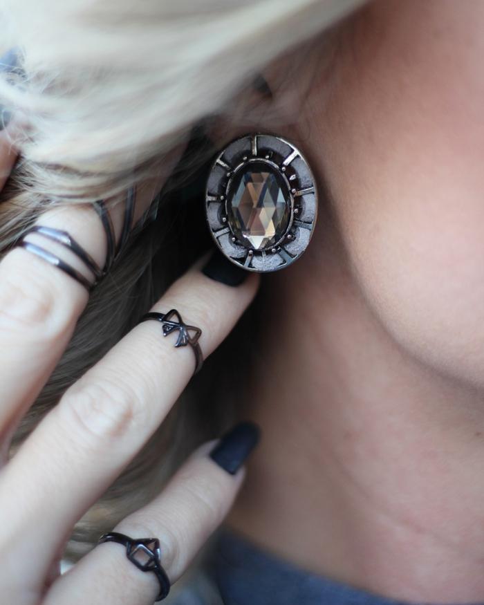 une bague fantaisie en plastique, bague triangle et anneau ruban associés à un vernis noir