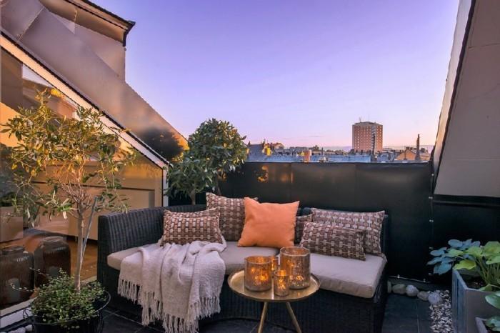 terrasse tropezienne style zen oriental, petite table en cuivre, canapé noir, plaid, plantes, carrelage noir, idée deco terrasse
