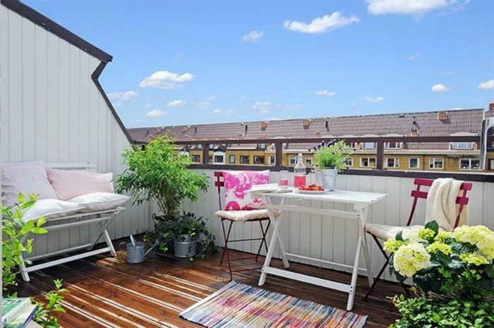 terrasse tropézienne, table blanche en bois et métal, chaises metalliques, plantes vertes, banc en bois pliant, petit tapis multicolore