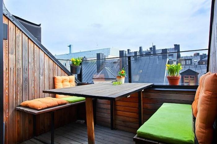 terrasse tropezienne en bois, table et bancs en bois, coissins d assise verts et coussins oranges, plantes