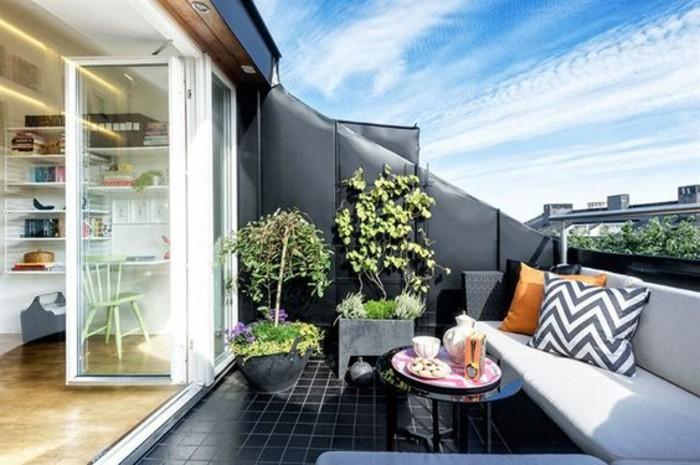 table basse noire, carrelage noir, canapé noi, coussin d'assise gris, plantes, idée tropezienne terrasse, vue sur la ville