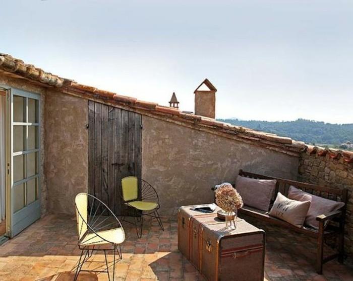 tropezienne terrasse style méditerranéen, chaises en métal, malle vintage en guise de table basse, banc en bois, coussins