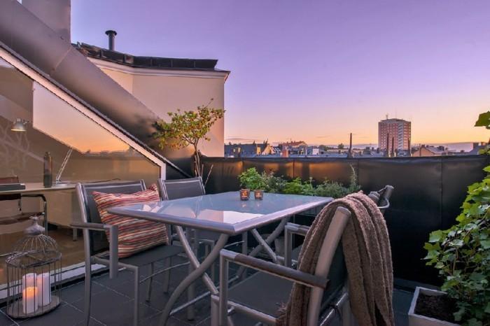 une terrasse tropézienne, carrelage noir, table grise, chaises en métal, plantes, paysage coucher du soleil, coin détente