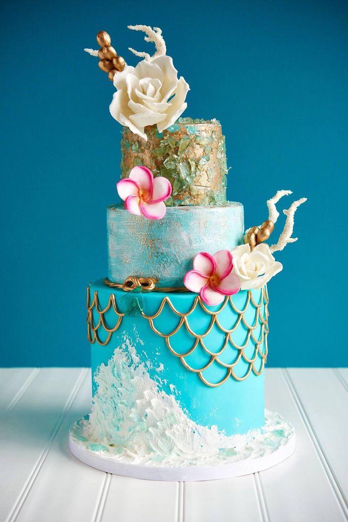 gateau motif sirene en blanc, bleu et or avec decoration fleurs chocolat blanc et fleurs rose et blanc fraiches
