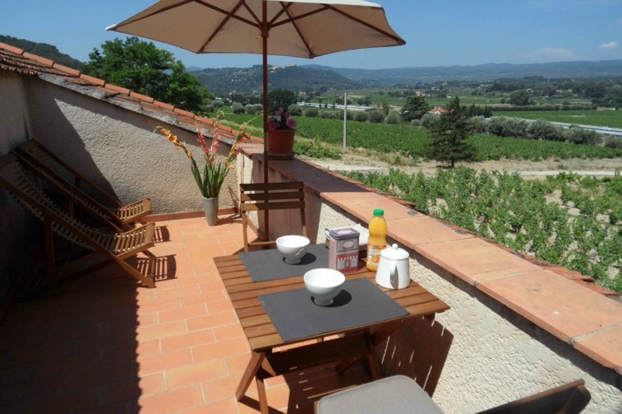 tropézienne terrasse, son el briques, chaises et table en bois, parasol, chaises longues en bois, plantes, maison rustique