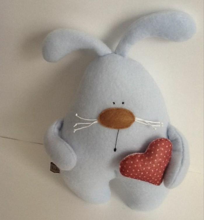 un-doudou-lapin-réalisé-avec-un-patron-lapin-modele-de-lapin-bleu-cousu-simple-avec-un-coeur-entre-les-pattes
