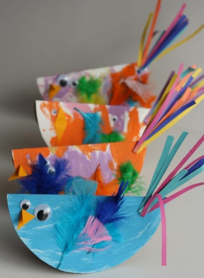 un-oiseau-en-papier-multicolore-decoration-plumes-de-couleurs-diverses-et-bande-de-papier-multicolores-en-guise-de-queue-des-yeux-mobiles-exemple-activité-créative-de-printemps