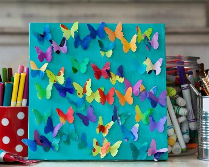 un-panneau-bleu-décoré-de-petits-papillons-en-papier-decoration-maison-multicolore-idée-d-activité-manuelle-printemps