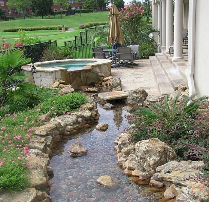 un-petit-bassin-d-eau-à-coté-de-l-entrée-d-une-maison-pierres-grosse-pierre-decoration-jardin-et-plantes-rocaille-vertes-idée-coin-zen-dans-un-jardin