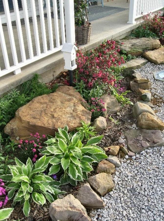 un-petit-coin-nature-près-d-une-palissade-grosse-pierre-decoration-jardin-galets-et-fleurs-pour-une-ambiance-fraiche