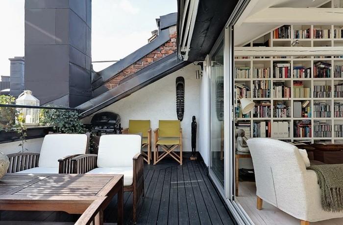 un coin lecture, bibliothèque ouverte sur une terrasse tropezienne, revêtement sol bois composite, table et chaises en bois, deux chaises pliantes