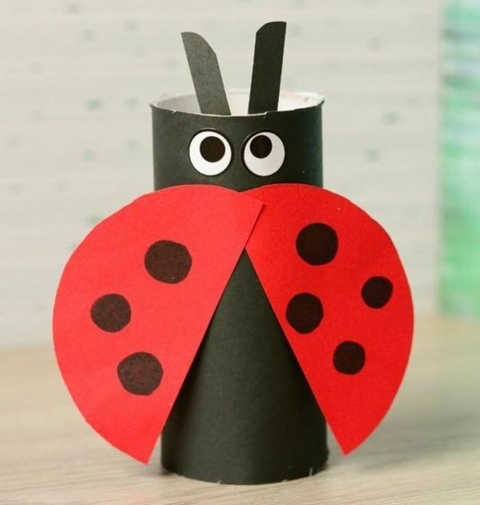 une coccinelle fabriquée à partir d'un rouleau papier toilette, des ailes rouges à points noirs, des yeux en papier, activité manuelle printemps maternelle