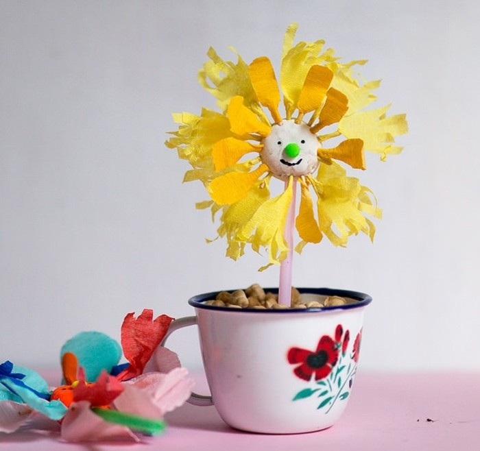 une-fleur-en-papier-dans-une-coupe-pleine-de-galets-fleur-à-pétales-jaunes-en-papier-crépon-idée-activité-manuelle-primaire