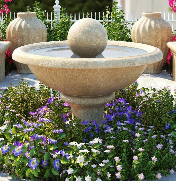 une fontaine en pierre, entouré de fleurs violettes et blanches en forme de cercle, une clôture blanche, deco exterieur, paysage exotique