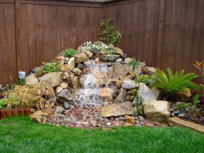 une-petite-chute-d-eau-un-tas-de-pierres-et-de-galets-petits-sarbustes-verts-idée-comment-faire-une-rocaille