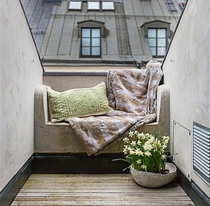 petit canapé en pierre, plaid et coussin vert pistache, des jonquilles, terrasse tropezienne composite et miniature