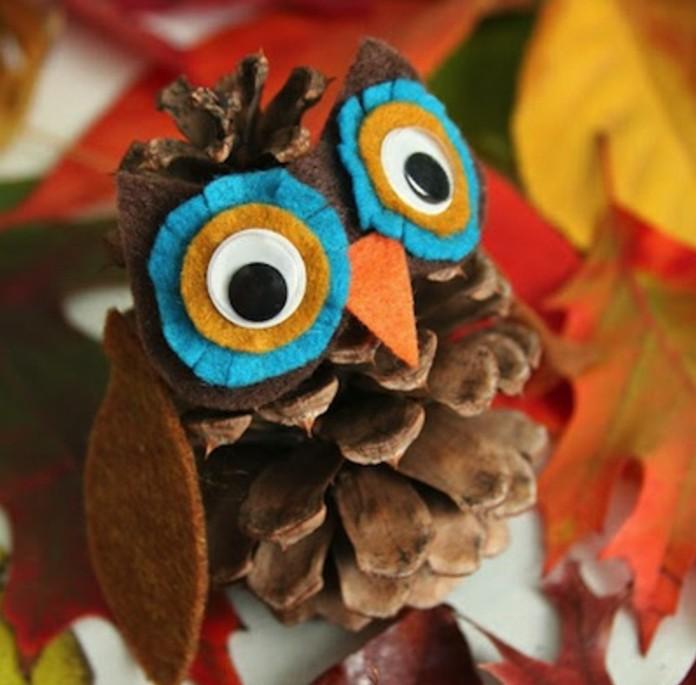 une pomme de pin transformée en hibou avec des yeux, bec et ailes en feutrine, activité manuelle automne maternelle