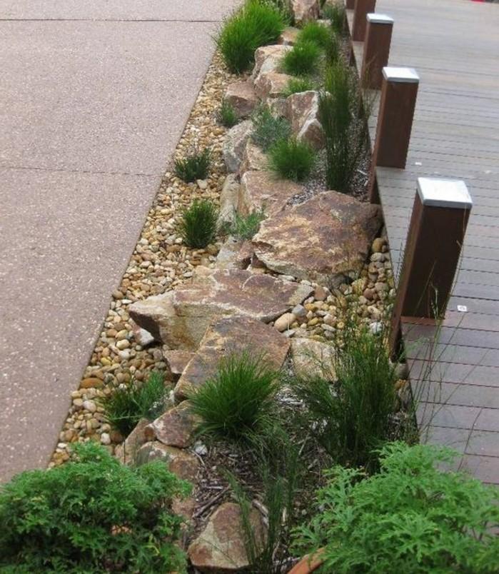une-rocaille-fleurie-longeant-une-allée-idée-comemnt-faire-une-rocaille-pierres-de-tailles-différentes-et-arbustes verts