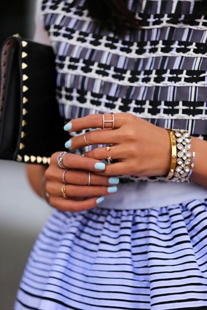 manucure couleur pastel et une accumulation d'anneaux, tendance fine bague