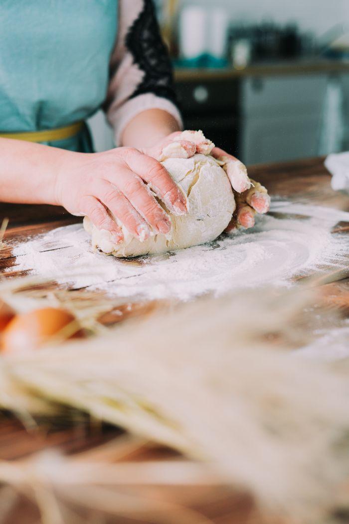 pétrir la pate à brioche sur une surface farinée pour faire un gateau pour paques, idee de dessert facile et rapide de pauqes