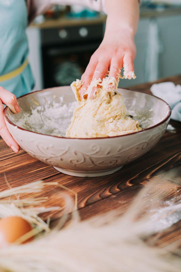 pétrir la pâte de mains dans un bol, idée dessert de paques faicle, brioche maison simple et rapide